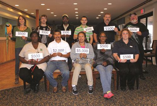 Among the winners in the Harrison Group's 27th Annual Employee Prize Drawing last month were, front, Valencia Sessoms, Bertin Bonala, Maria Hernandez, Marian Thompson and Heidi Carpenter; and, back, Dawn Hahn with Harrison Group mascot Dakota, Steven Olischar, Russell Parker, Ionut Sofan, Robert Walter and Wayne Hudson. Submitted Photos