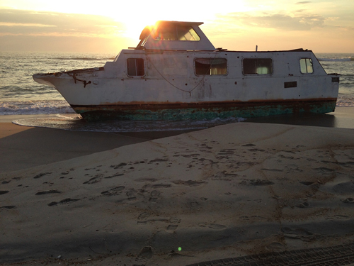 Local residents and artists Kirk McBride and Lynne Lockhart came upon this 40-foot houseboat on Thursday morning during a walk along the beach on Assateague Island. Photo by Kirk McBride