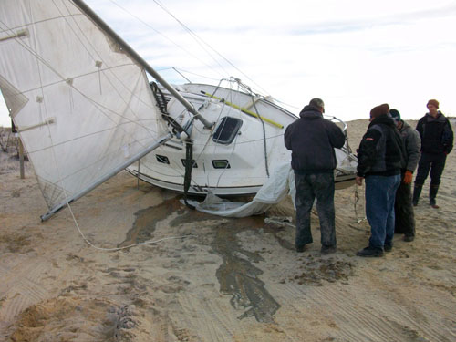 Cropper & Sons Towing and Recovering is pictured removing the 26-foot sail boat from the Assateague State Park beach on Monday morning. Photo by Travis Brown