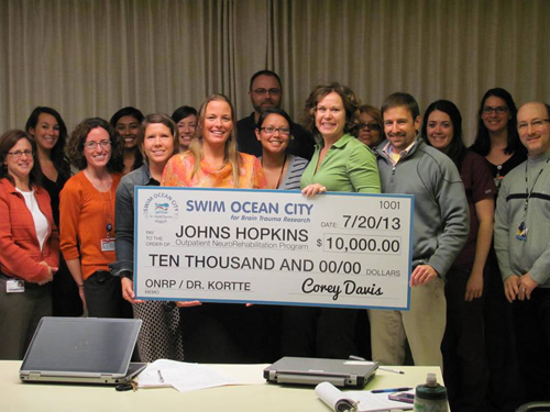 Swim Ocean City organizer Corey Davis and his team presented a $10,000 check to the Johns Hopkins Outpatient Neuro Rehabilitation Program, representing proceeds from the first-ever event held in Ocean City last summer. Submitted Photo