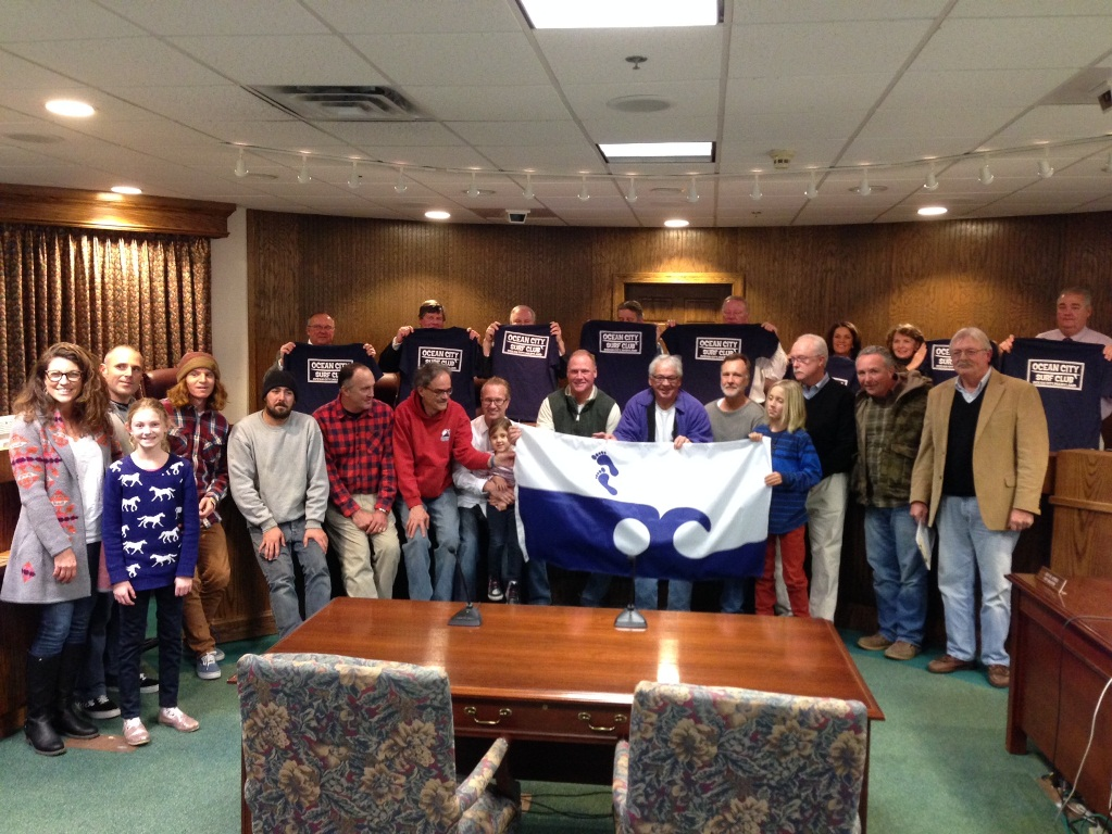 "Supporters and members of the new Ocean City Surf Club are pictured with the Mayor and Council. The flag represents the ""leave only your footprints behind"" campaign the club will now be leading. Photo by Joanne Shriner"