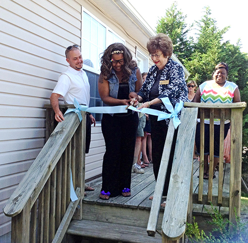 With help from Habitat Board of Directors President Josh Esworthy and County Commissioner Judy Boggs, Jessica Spence cuts the ribbon on her Habitat for Humanity of Worcester County home in Snow Hill.