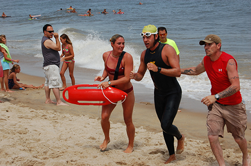 After completing the nine-mile ocean swim last year, participants Timothy Stang is pictured receiving support from a member of the Ocean City Beach Patrol and a volunteer. Submitted Photo