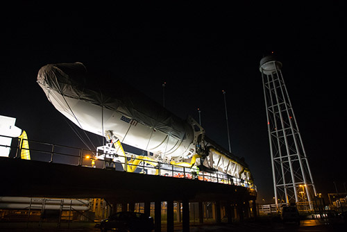 The Antares rocket, pictured being loaded into position, will deliver 3,300 pounds of supplies to the International Space Station. Photo courtesy of Wallops