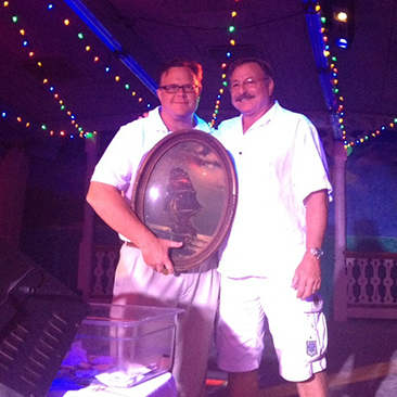 O.C. Seacrets, Inc. President Leighton Moore presents Vice President Gary Figgs with a framed Seacrets Spirits logo that Moore designed in recognition of Figgs' dedication to launching the new products. Photo by Joanne Shriner