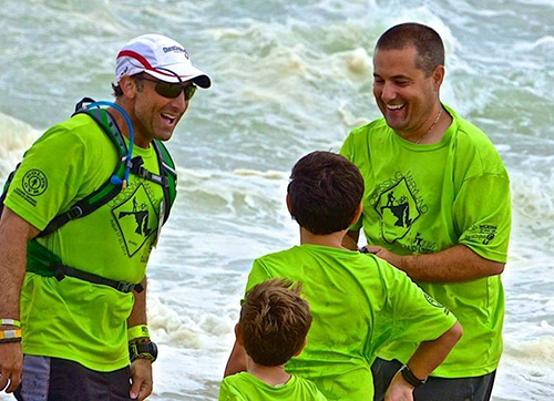 Justin Berk, left, is met at the Inlet last Saturday by his two sons and Dennis Devoe, who he called his team leader, navigator, triage nurse and biggest supporter. Photo by Lori Martin