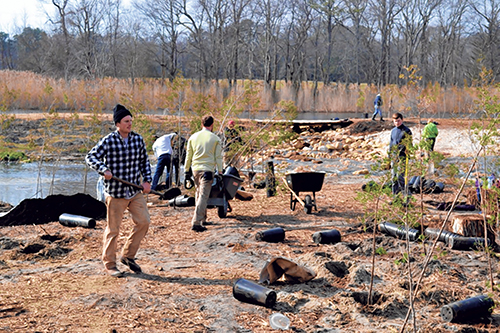 Volunteers are pictured continuing restorative work at the site of the Bishopville dam. Photo by Charlene Sharpe