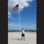 Smith is pictured with the flag pole he assembled along with a group of strangers last Sunday on Dog and Bitch Island in the Isle of Wight Bay. Submitted Photos