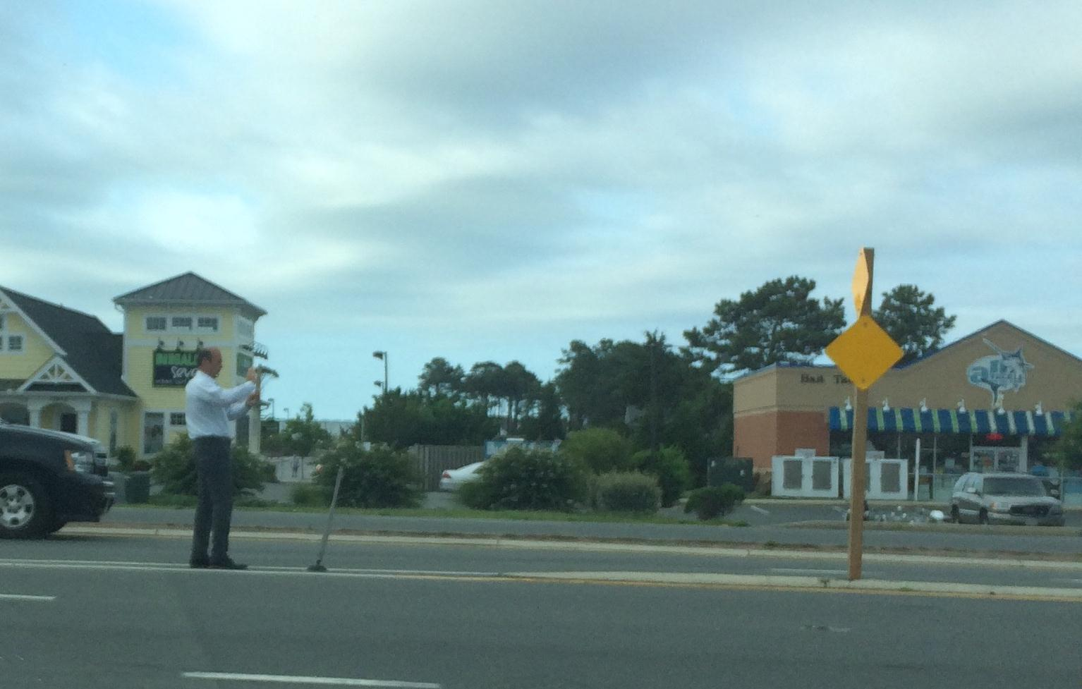 City Manager David Recor is pictured this morning taking photos of the replacement sign he knocked down last Friday on Route 50.