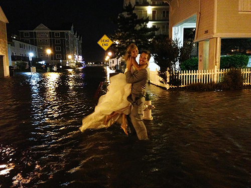 Mollie and Josh Kotis are pictured in a flooded downtown area making their way to the Emerson Towers where they would spend their wedding night. Photos by Lloyd E. Branson and Jordan Farrell