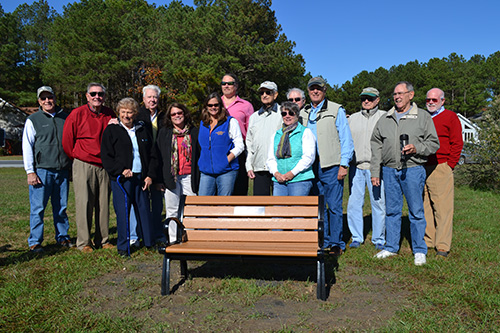 The community service of Bob Abele, center with white hat, was celebrated last week with the installation and dedication of a bench in his honor in Ocean Pines. Photo by Charlene Sharpe