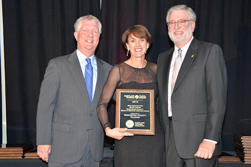 Frederick County Tourism Director John Feisler and Prince George's County Tourism Executive Director Matt Neitzy present Worcester County Tourism Director Lisa Challenger, center, with the Best Destination Guide Award for the Beach and Beyond Visitor's Guide during the 2015 Maryland Travel and Tourism Summit. Submitted Photo