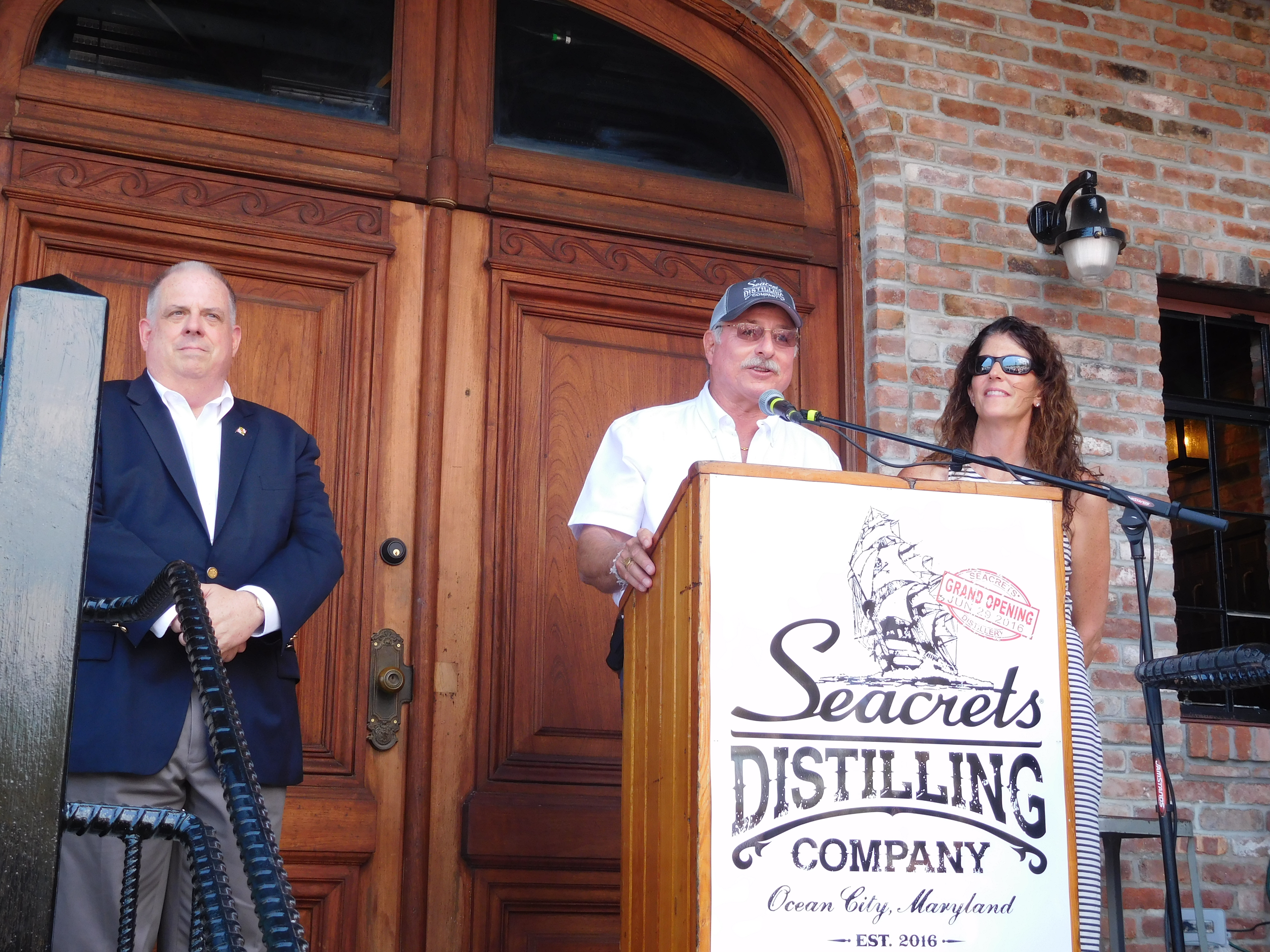 Seacrets owner Leighton Moore speaks at Wednesday's ribbon cutting of the new distillery. Also pictured are Gov. Larry Hogan and Moore's wife, Rebecca. Photo by Terri French