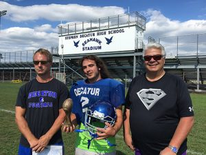 "The first ""Tough Guy of the Week"" award went to Decatur's Eddie Zonnak, who scored a late touchdown in the Seahawks' comeback attempt in a 20-14 loss to Bohemia Manor last Friday. Pictured above is Zonnak (center) flanked by Coach Stan Griffin (left) and Atlantic Physical Therapy President and CEO Bob Hammond (right).  Submitted photo"