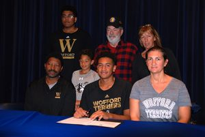 Decatur standout center Keve Aluma last week signed a national letter of intent to continue his career at Wofford next year. Aluma (center) signed the letter of intent surrounded by parents and family.  Photo by Shawn Soper
