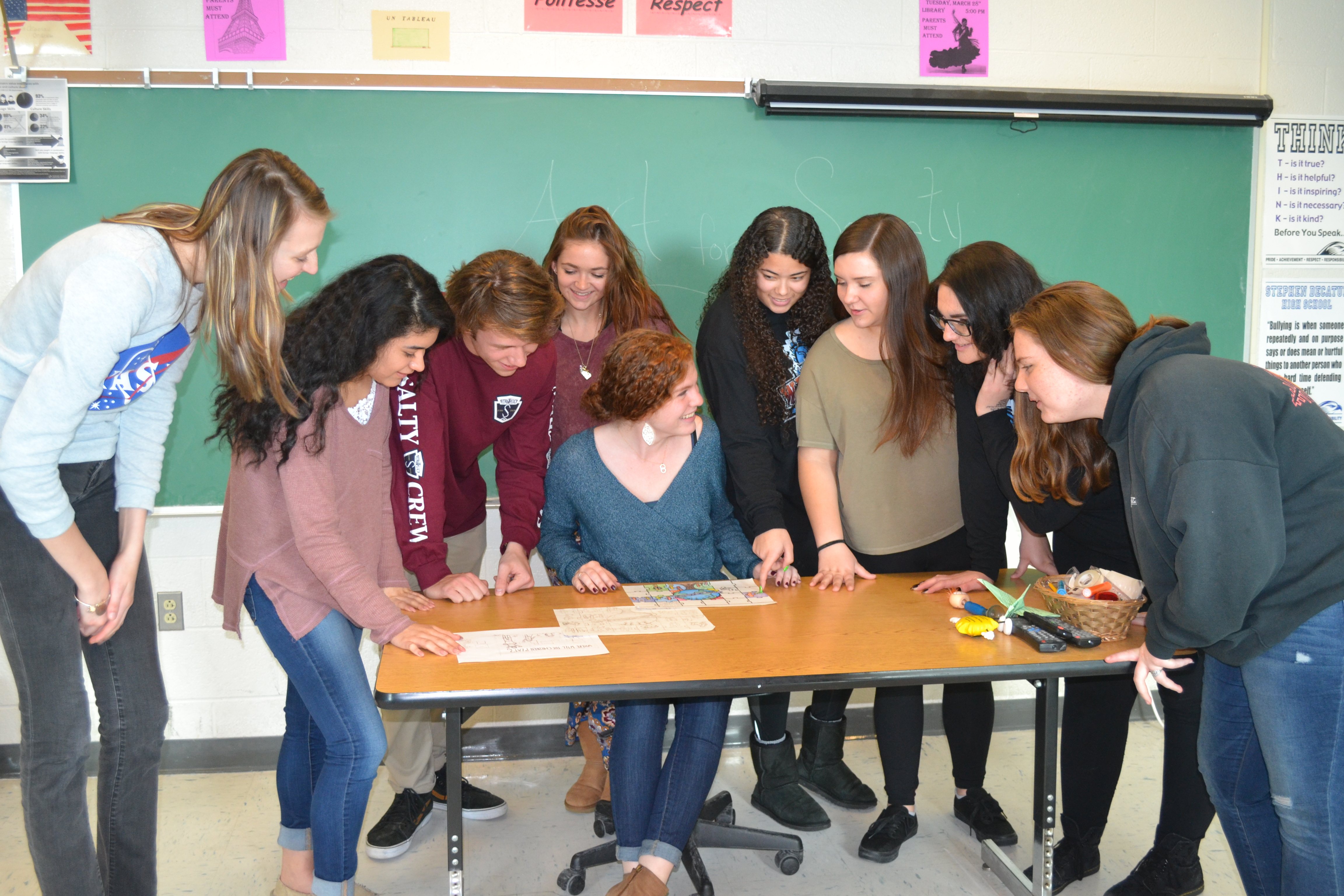 Foreign Language Club members from Stephen Decatur High School are pictured looking over designs for their traveling mural project. Photo by Charlene Sharpe
